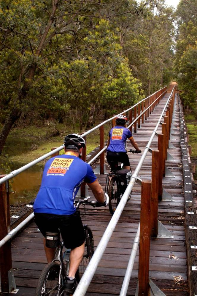 Crossing the timber railway bridge over St John Brook. (Department of Environment and Conservation and Munda Biddi Trail Foundation)